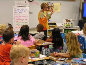 Photo of teacher in a classroom holding a book up as she stands before her 4th-or-5th-grade-sized students at their desks
