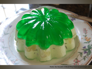 Jello mold on a plate, the bottom half is opaque and cream-colored, with embedded bits of other food; the top layer is clear green jello