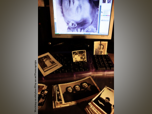 Family snapshots laid out across a computer keyboard, with a scanned image from another snapshot visible on the computer monitor