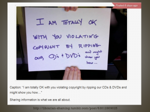 """Photo of two hands holding up a andwritten sign that says """"I am totally okay with you violating copyright by ripping our CDs & DVDs... and might show you how"""""""