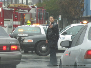 Photo of a policewoman directing traffic in the rain, with police cars and a fire truck behind her