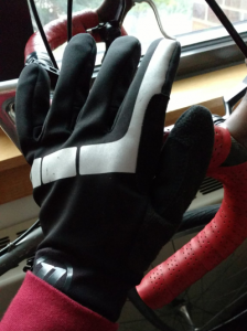 Full hand in lightweight black glove with reflective gray stripe. Hand is resting on bike handlebars, which are leaning against a windowsill in the background.