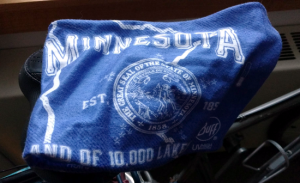 Light blue square of fabric draped over barely visible narrow black bike seat. The fabric has white printing with an outline of the state of Minnesota, and the state seal in the center.