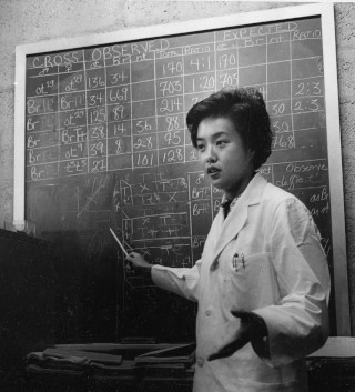 Black and white midcentury photograph of Chinese woman scientist in white lab coat gesturing in front of a chalkboard full of data