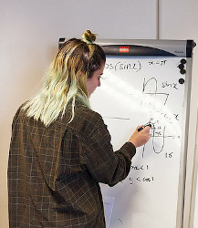 White woman with long multi-hued hair faces a whiteboard, working out a math problem